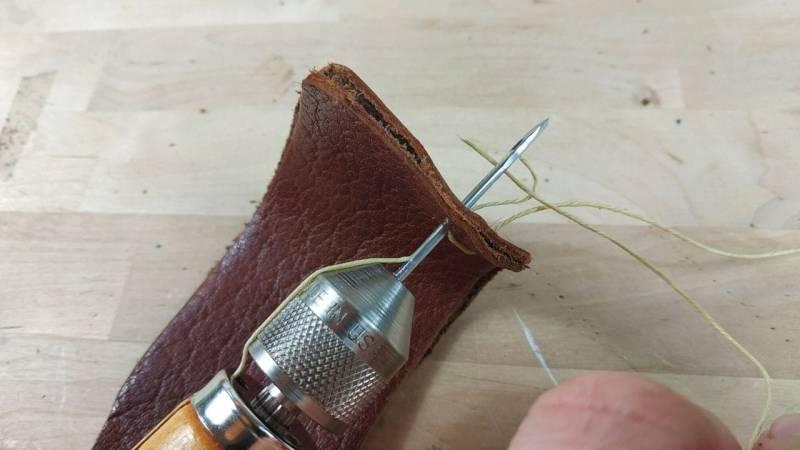 Ziehe die Nadel wieder etwas zurück, sodass eine Schlaufe entsteht. Durch diese Schlaufe steckst du nun den restlichen Faden.