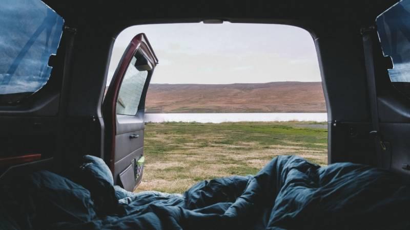 Eine dicke Decke und ein Schlafsack sind ein Muss beim Camping im Auto