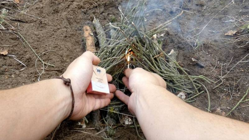 Setze dein Streichholz nun so bei deinem Anzündmaterial an, dass die Flamme die feinen Stöckchen berührt.