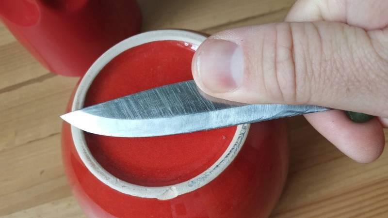Der unglasierte Boden einer Porzelantasse sind perfekt zum schärfen eines Messers